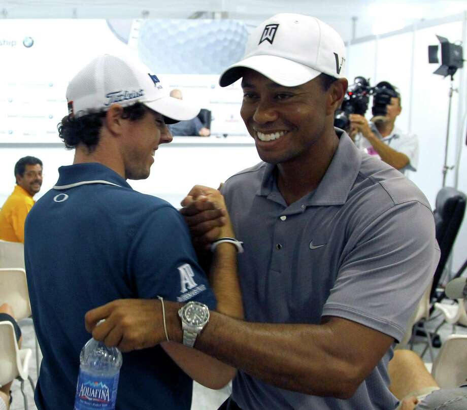 Rory McIlroy of Northern Ireland, left, shakes hands with Tiger Woods between interviews during the Pro-Am of the BMW Championship PGA golf tournament at Crooked Stick Golf Club in Carmel, Ind., Wednesday, Sept. 5, 2012. (AP Photo/Charles Rex Arbogast) Photo: Charles Rex Arbogast, Associated Press / AP