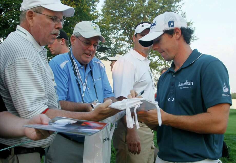 Rory McIlroy of Northern Ireland, right, signs autographs during the Pro-Am tournament of the BMW Championship PGA golf tournament at Crooked Stick Golf Club in Carmel, Ind., Wednesday, Sept. 5, 2012. (AP Photo/Charles Rex Arbogast) Photo: Charles Rex Arbogast, Associated Press / AP