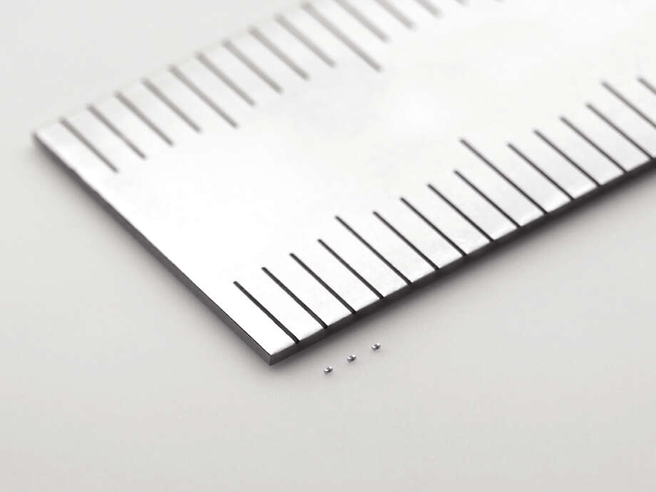 In this undated photo released by Murata Manufacturing Co., its latest capacitors, measuring just 0.25 millimeter by 0.125 millimeter, are shown next to a ruler. Small is big for Murata: The Japanese electronics maker has developed the world's tiniest component known as the capacitor. And that's big business. Capacitors, which store electric energy, are used in the dozens, even in the hundreds, in just about every type of gadget - smartphones, laptops, hybrid cars, medical equipment and digital cameras. (AP Photo/Murata Manufacturing Co.) NO SALES Photo: Associated Press / Murata Manufacturing Co.