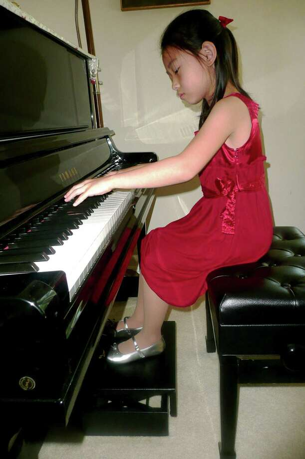 Young piano prodigy Stephanie Chang, age six, plays passionately at her Riverside home. The pedals of her instrument have been raised so her feet can reach them. Photo: Anne W. Semmes