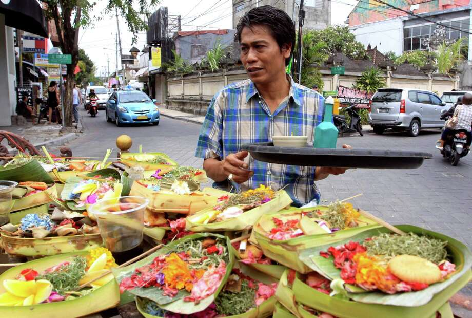 This Aug. 25, 2012 photo shows a Balinese man offering food to local god in Kuta, Bali, Indonesia. It can be hard to find Bali's serenity and beauty amid the villas with infinity pools and ads for Italian restaurants. But the rapidly developing island's simple pleasures still exist, in deserted beaches, simple meals of fried rice and coconut juice, and scenes of rural life. (AP Photo/Firdia Lisnawati) Photo: Firdia Lisnawati / AP