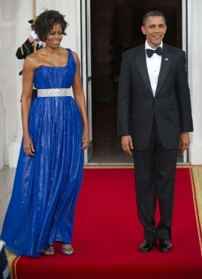 Michelle Obama and President Barack Obama wait on the red carpet for the arrival of the Mexican President and his wife May 19, 2010 on the North Portico at the State Dinner for Mexico at the White House in Washington, DC.      (PAUL J. RICHARDS / AFP/Getty Images)