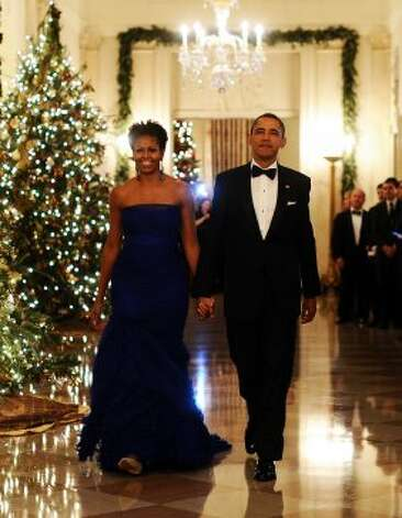 President Obama and Michelle arrive in the East Room of the White House to attend a reception for Kennedy Center Honorees in Washington, DC, on December 4, 2011. Mrs. Obama's strapless gown was designed by Vera Wang.  (JEWEL SAMAD / AFP/Getty Images)