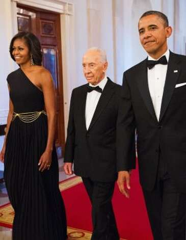 President Barack Obama (R) and First Lady Michelle Obama, dressed in a one-shoulder Michael Kors gown, enter the East Room with Israeli President Shimon Peres for a dinner where he would be presented with the Presidential Medal of Freedom June 13, 2012 at the White House in Washington, DC.  (AFP/Getty Images)