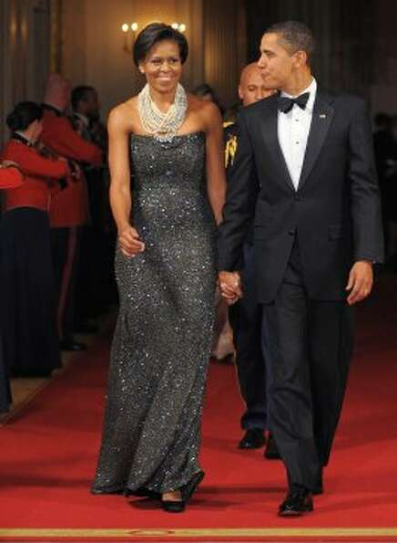 President Barack Obama and first lady Michelle Obama make their way into the East Room for after din