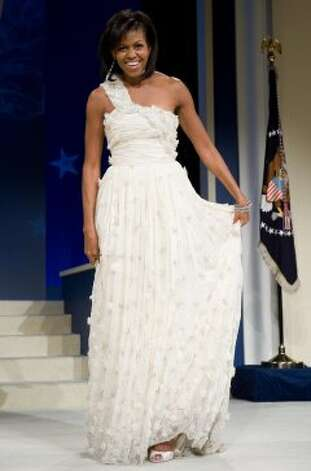 First Lady Michelle Obama poses during the Inaugural Ball in Washington, DC, on January 20, 2009. Obama's white chiffon dress designed by  Jason Wu now resides on display in the Smithsonian.  (SAUL LOEB / AFP/Getty Images)
