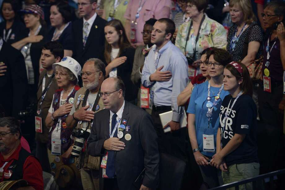 Supporters listen to the National Anthem at the Time Warner Cable Arena in Charlotte, North Carolina, on September 5, 2012 on the second day of the Democratic National Convention (DNC). The DNC is expected to nominate US President Barack Obama to run for a second term as president on September 6. Photo: BRENDAN SMIALOWSKI, AFP/Getty Images / AFP