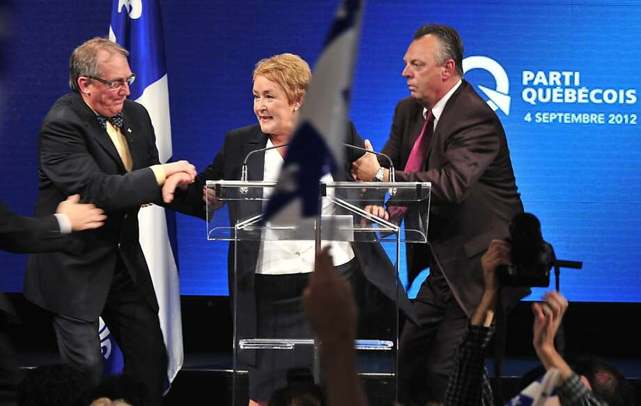 Pauline Marois is whisked offstage because of gunfire outside as she delivers her victory speech on becoming the first female premier in Quebec history. Photo: Paul Chiasson, Associated Press