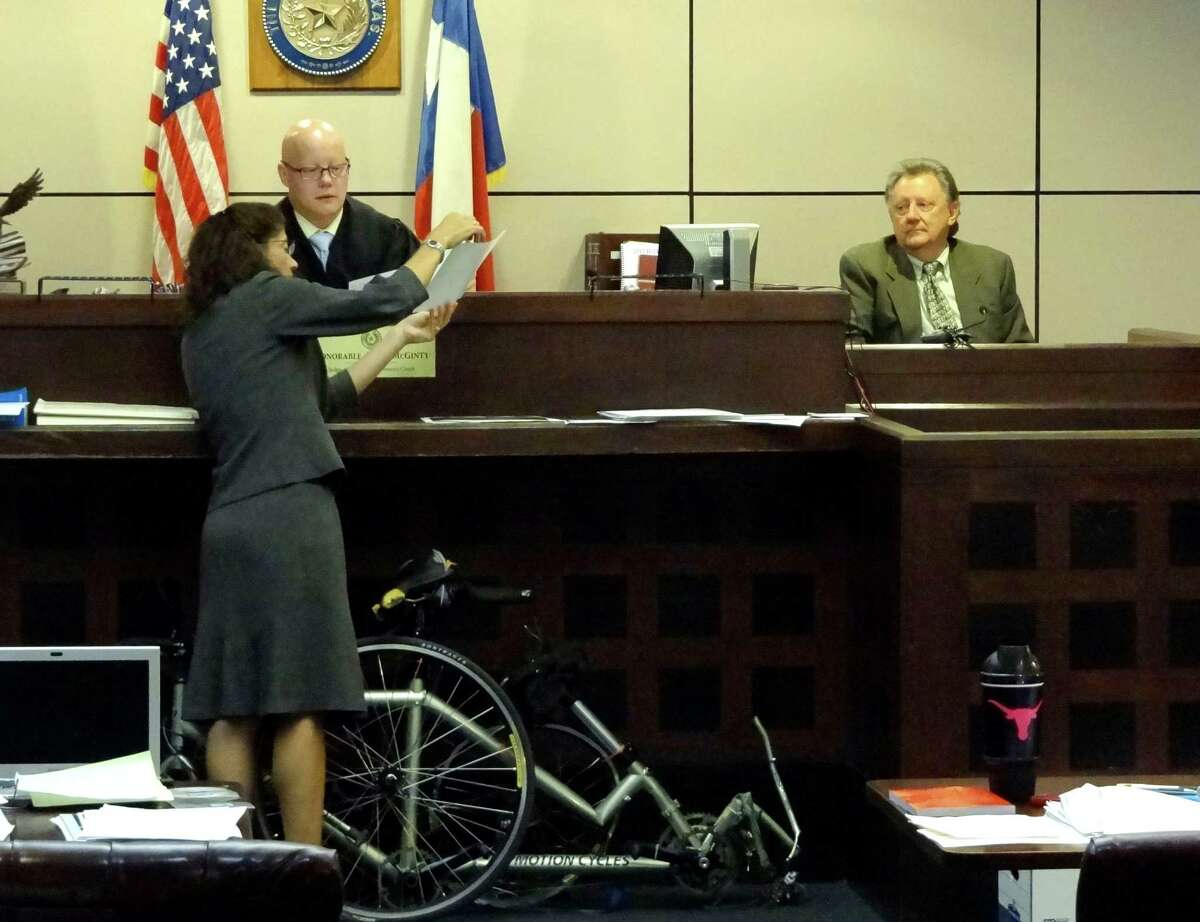 Prosecutor Lorina Rummel shows a picture to Judge Angus McGinty as expert witness Charles R. Ruble, right, watches during a hearing related to the criminally negligent homicide trial of Gilbert John Sullaway in 144th District Court on Wednesday, Sept. 5, 2012. Sullaway hit and killed two cyclists on Texas 16 three years ago. The broken bicycle that belonged to Gregory and Alexandra Bruehler sits on the floor.