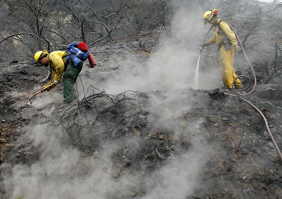 Eric Smith (left) and James Heaton from San Diego work to clean up hotspots in the Angeles National Forest blaze in the San Gabriel Mountains. Photo: Nick Ut, Associated Press