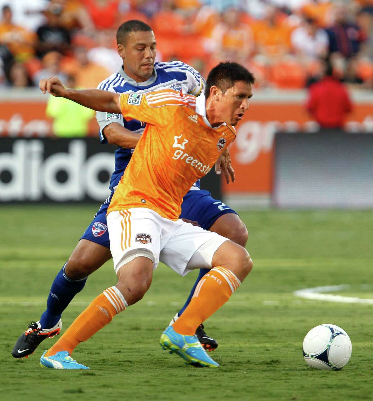 FC Dallas' Fabian Castillo left, and the Houston Dynamo forward Brian Ching chase down the ball during the first half of MLS game action at BBVA Compass Stadium Saturday, June 16, 2012, in Houston. ( James Nielsen / Chronicle )