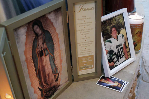 A photo of Andres Cabrera Cordero sits beside a candle and an image of the Lady of Guadalupe on Wednesday, Sept. 5, 2012. Cordero, 19, was killed in an auto accident at the intersection of Sonterra and Sigma Roads. Cordero was a 2012 graduate of Reagan High School and driving to San Antonio College when he lost his life after colliding with the utility pole and fire hydrant. Photo: Kin Man Hui, SAN ANTONIO EXPRESS-NEWS / ©2012 San Antonio Express-News