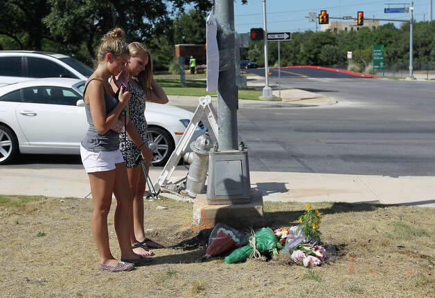 Two young women (no identities given) reflect on the loss of their friend Andres Cabrera Cordero who died from a collision with a utiility pole and fire hydrant at the intersection of Sigma and Sonterra Roads on Wednesday, Sept. 5, 2012. Cordero graduated from Reagan High School and was driving to San Antonio College when the accident occurred around 6 a.m. Photo: Kin Man Hui, SAN ANTONIO EXPRESS-NEWS / ©2012 San Antonio Express-News