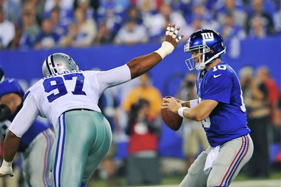 New York Giants quarterback Eli Manning (10) avoids Dallas Cowboys defensive end Jason Hatcher (97) while looking to pass during the first half of an NFL football game Wednesday, Sept. 5, 2012, in East Rutherford, N.J. (AP Photo/Bill Kostroun) Photo: Bill Kostroun, Associated Press / FR59151 AP