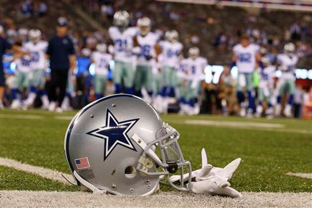 A Dallas Cowboys helmet is shown on the field as the team warms up before an NFL football game against the New York Giants at MetLife Stadium Wednesday, Sept. 5, 2012, in East Rutherford, N.J. (AP Photo/Julio Cortez) Photo: Julio Cortez, Associated Press / AP
