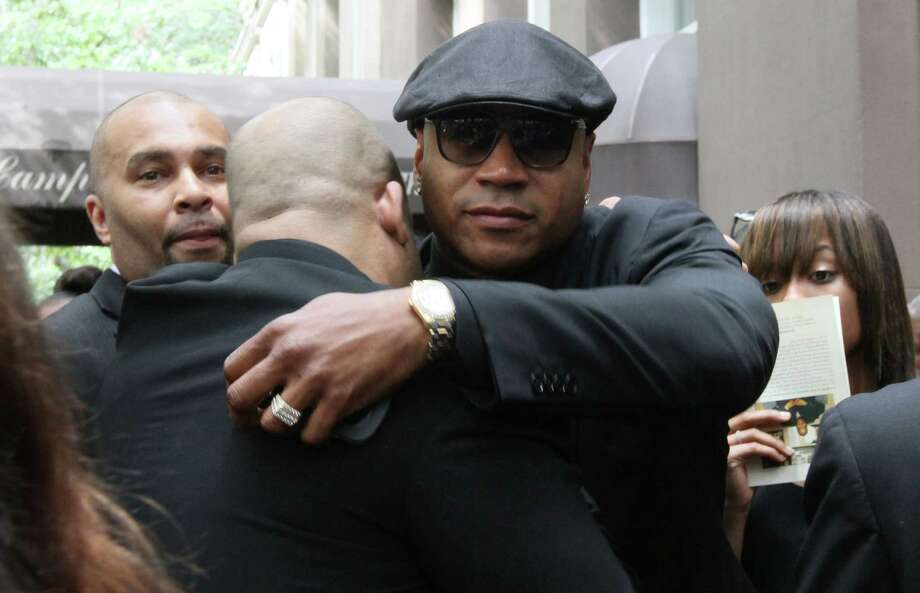 "LL Cool J, foreground right, shares an embrace with another as he leaves the Frank E. Campbell Funeral Chapel following the service for hip-hop mogul Chris Lighty, Wednesday Sept. 5, 2012 in New York.  Mourners in the packed chapel Wednesday included Sean ""Diddy"" Combs, Missy Elliott, Q-Tip, LL Cool J, Russell Simmons, 50 Cent and Grandmaster Flash. Lighty, the 44-year-old hip-hop mogul was found dead in his Bronx apartment last week with a gunshot wound to the head. Photo: Tina Fineberg, Associated Press / FR73987 AP"