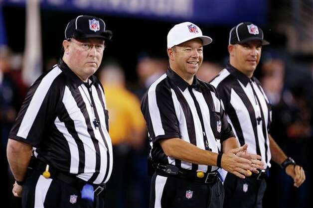 Referee Jim Core, center, gestures alongside other game officials before an NFL football game between the New York Giants and the Dallas Cowboys, Wednesday, Sept. 5, 2012, in East Rutherford, N.J. (AP Photo/Julio Cortez) Photo: Julio Cortez, Associated Press / AP