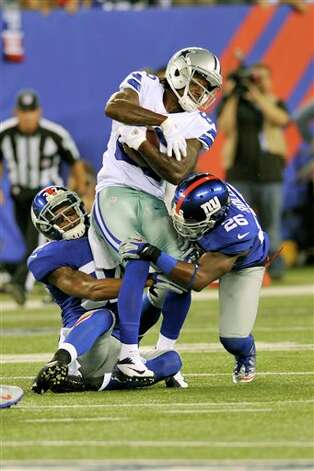Dallas Cowboys' Felix Jones, center, is brought down by New York Giants' Michael Coe, left, and Antrel Rolle during the first half of an NFL football game Wednesday, Sept. 5, 2012, in East Rutherford, N.J. (AP Photo/Bill Kostroun) Photo: Bill Kostroun, Associated Press / AP2012
