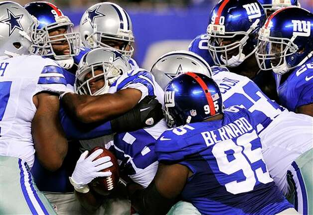 Dallas Cowboys running back Felix Jones (28) is tackled by New York Giants defensive tackle Rocky Bernard (95) during the first half of an NFL football game, Wednesday, Sept. 5, 2012, in East Rutherford, N.J. (AP Photo/Bill Kostroun) Photo: Bill Kostroun, Associated Press / FR59151 AP