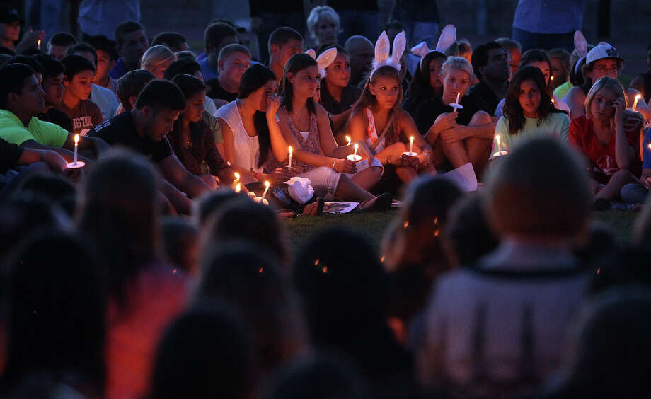 Several hundred friends and former classmates of Andres Cabrera Cordero gather for a candlelight vigil and remembrance at Reagan High School on Wednesday, Sept. 5, 2012. Cordero, 19, was killed in an auto accident at the intersection of Sonterra and Sigma Roads. Cordero was a 2012 graduate of Reagan High School and driving to San Antonio College when he lost his life after colliding with the utility pole and fire hydrant. Cordero's mother, Marcela (shown in a black blouse), joined her son's friends at the memorial. Photo: Kin Man Hui, SAN ANTONIO EXPRESS-NEWS / ©2012 San Antonio Express-News