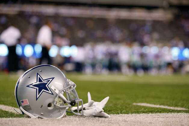 A Cowboys helmet rests on the field before an NFL football game between the New York Giants and the Dallas Cowboys. Photo: Julio Cortez, Associated Press / AP