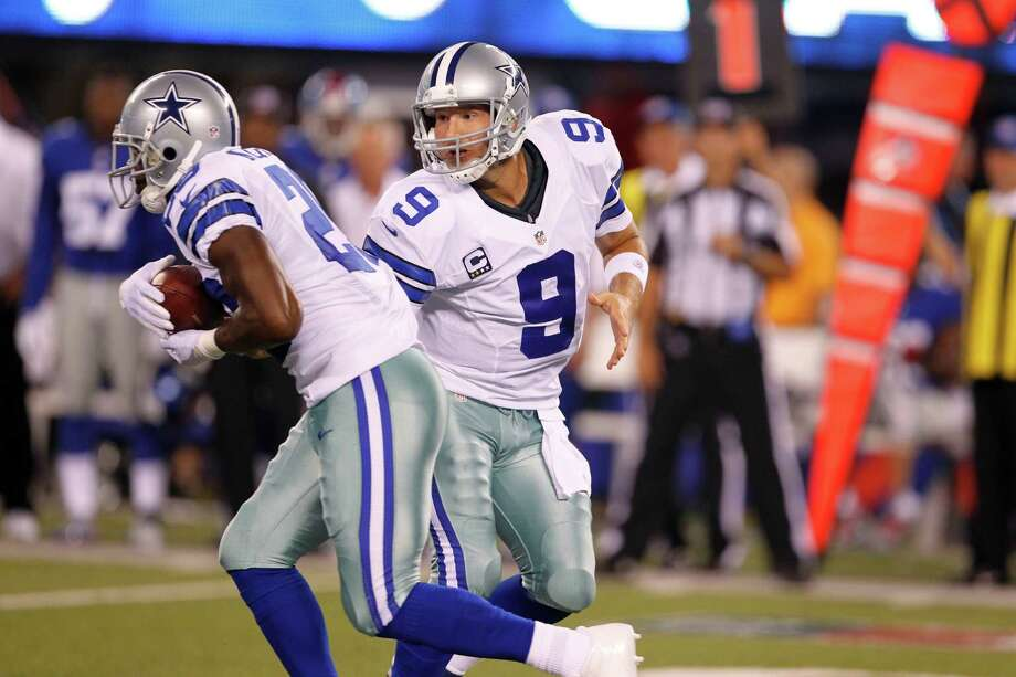 Cowboys quarterback Tony Romo, right, hands off to  Felix Jones during the first half. Photo: Julio Cortez, Associated Press / AP