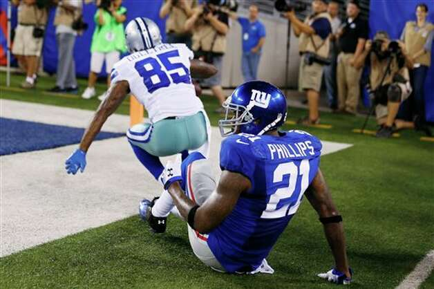New York Giants strong safety Kenny Phillips (21) reacts as Dallas Cowboys wide receiver Kevin Ogletree (85) celebrates catching a touchdown pass during the second half of an NFL football game Wednesday, Sept. 5, 2012, in East Rutherford, N.J. (AP Photo/Julio Cortez) Photo: Julio Cortez, Associated Press / AP