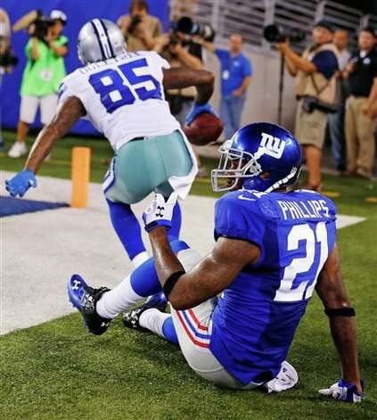 New York Giants strong safety Kenny Phillips (21) reacts as Dallas Cowboys wide receiver Kevin Ogletree (85) celebrates catching a touchdown pass during the second half of an NFL football game, Wednesday, Sept. 5, 2012, in East Rutherford, N.J. (AP Photo/Julio Cortez) Photo: Julio Cortez, Associated Press / AP2012