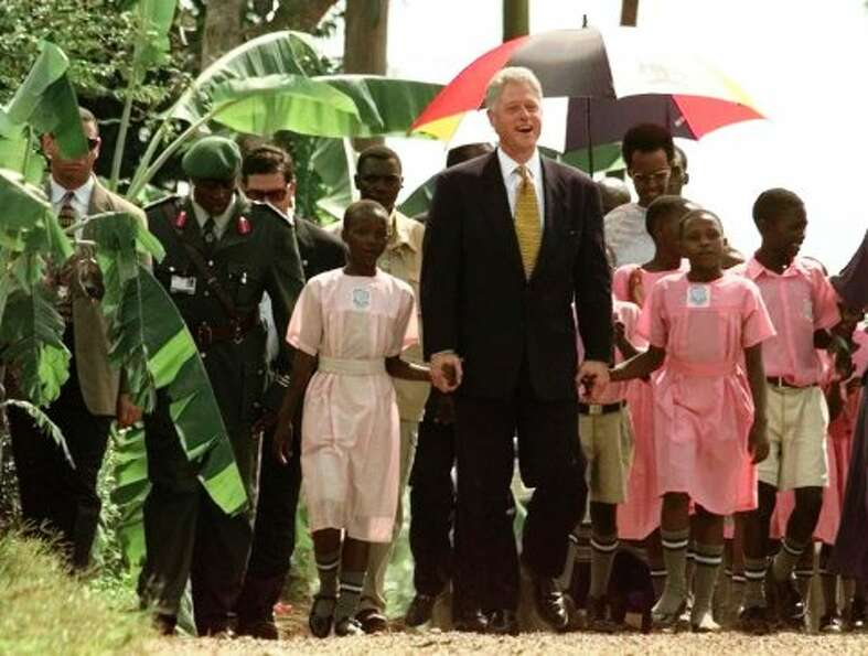 FILE - In this March 24, 1998, file photo President Bill Clinton is escorted by children of the Kiso