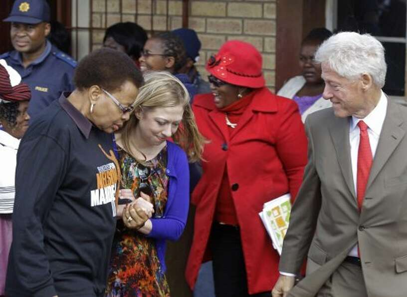 South Africa's Graça Machel, left, walks with Chelsea Clinton, second left, and her dad former Amer