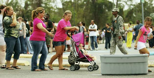 A Louisiana National Guard soldier keeps watch as residents wait in line to apply for disaster food assistance on September 5, 2012 in Westwego, Louisiana. Hundreds were waiting in line for hours in the heat to apply for the Disaster Supplemental Nutrition Assistance Program for those affected by Hurricane Isaac. Photo: Mario Tama, Getty Images / 2012 Getty Images