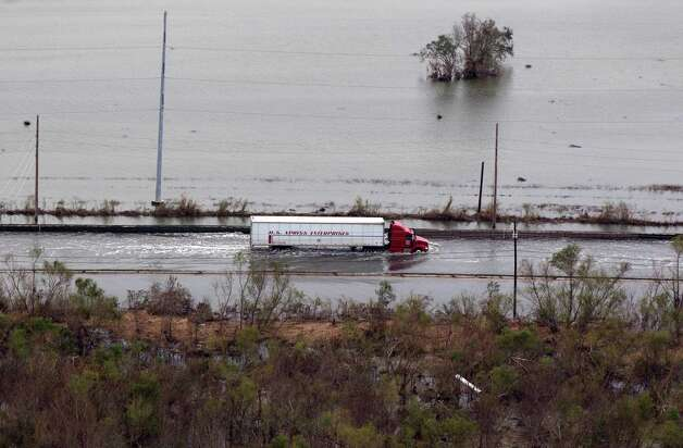 This aerial photo shows a tractor trailer driving through floodwaters on Hwy 23 in the aftermath of Hurricane Isaac in Plaquemines Parish, La., Wednesday, Sept. 5, 2012. Photo: Gerald Herbert, Associated Press / AP