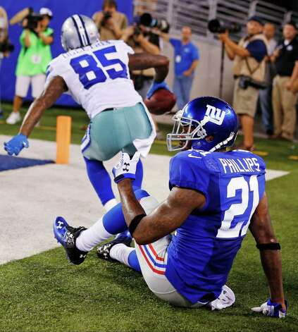New York Giants strong safety Kenny Phillips (21) reacts as Dallas Cowboys wide receiver Kevin Ogletree (85) celebrates catching a touchdown pass during the second half of an NFL football game, Wednesday, Sept. 5, 2012, in East Rutherford, N.J. (AP Photo/Julio Cortez) Photo: Julio Cortez / AP