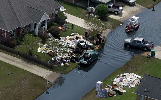 In this aerial photo, people clear out their flooded homes in the aftermath of Hurricane Isaac. in LaPlace, La., Wednesday, Sept. 5, 2012. Thousands of electric customers are still without power, hundreds remained in shelters and several miles of coast line was tarred with weathered oil washing ashore, days after Isaac raked Louisiana. Photo: Gerald Herbert, Associated Press / AP