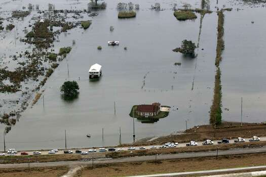 This aerial photo shows flooded homes and a convoy of escorted residents waiting to leave the area in the aftermath of Hurricane Isaac, Wednesday, Sept. 5, 2012, in Plaquemines Parish, La. Photo: Gerald Herbert, Associated Press / AP