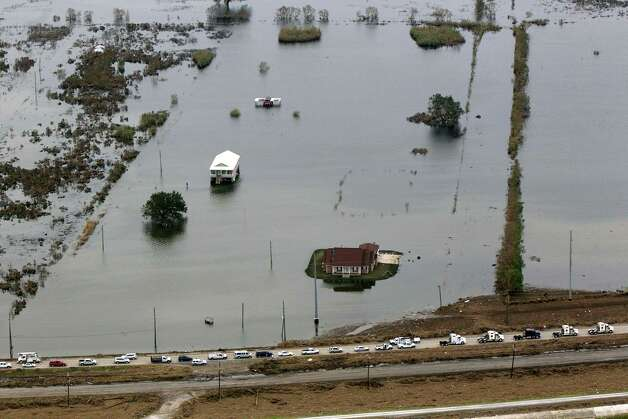 HURRICANE ISAAC: This aerial photo shows flooded homes and a convoy of escorted residents waiting to leave the area in the aftermath of Hurricane Isaac, Sept. 5, 2012, in Plaquemines Parish, La. Photo: Gerald Herbert, Associated Press / AP