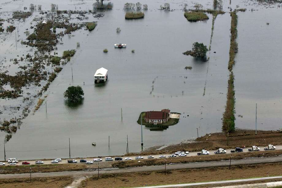 HURRICANE ISAAC:This aerial photo shows flooded homes and a convoy of escorted residents waiting to leave the area in the aftermath of Hurricane Isaac, Sept. 5, 2012, in Plaquemines Parish, La. Photo: Gerald Herbert, Associated Press / AP