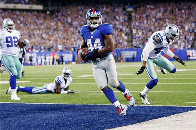 New York Giants running back Ahmad Bradshaw (44) scores a touchdown during the second half of an NFL football game against the Dallas Cowboys Wednesday, Sept. 5, 2012, in East Rutherford, N.J. (AP Photo/Julio Cortez) Photo: Julio Cortez, Associated Press / AP