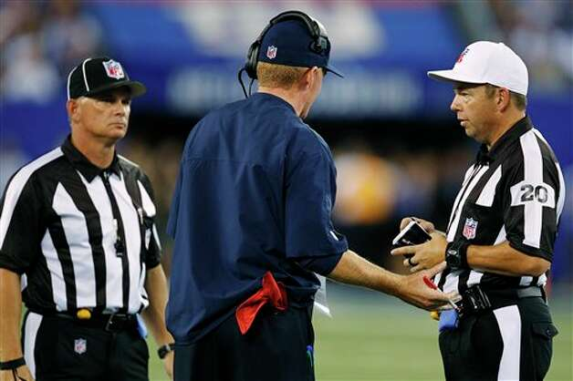 Dallas Cowboys head coach Jason Garrett, center, argues with referee Jim Core (20) during the first half of an NFL football game against the New York Giants, Wednesday, Sept. 5, 2012, in East Rutherford, N.J. (AP Photo/Julio Cortez) Photo: Julio Cortez, Associated Press / AP