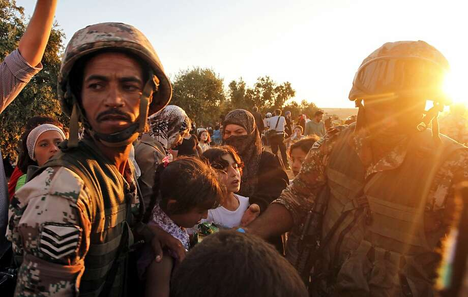 Newly-arrived Syrian refugee families receive food from the Jordanian military after they crossed the border from Tal Shehab city in Syria, through the Al Yarmouk River valley, into Thnebeh town, in Ramtha , Jordan,  Wednesday, Sept. 5, 2012.  More than 100,000 Syrians fled their country in August, the highest monthly total since the crisis began in March 2011, the U.N. refugee agency said Tuesday. That exodus sharply increased the number of Syrians now living in neighboring countries, bringing the total number of refugees to 234,368 in the past 17 months, the agency said. Photo: Mohammad Hannon, Associated Press
