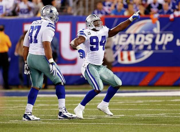 Dallas Cowboys linebacker DeMarcus Ware (94) reacts after sacking New York Giants quarterback Eli Manning, not pictured, as teammate  Jason Hatcher (97) looks on during the first half of an NFL football game Wednesday, Sept. 5, 2012, in East Rutherford, N.J. (AP Photo/Julio Cortez) Photo: Julio Cortez, Associated Press / AP