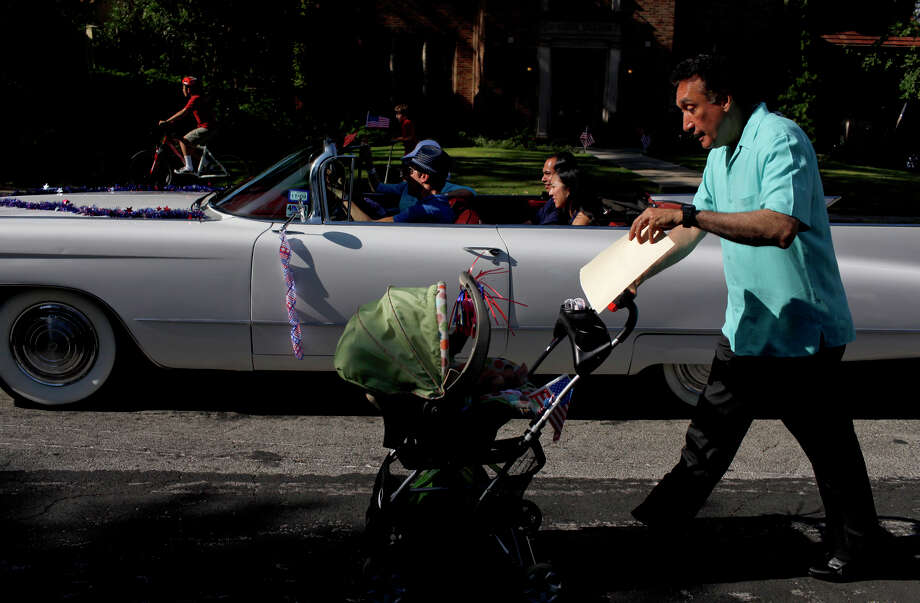 Former Mayor Henry Cisneros, right, fans Carina Castro, 3 1/2 months, as he pushes her stroller next to the car driving Castro's parents, Mayor Julian Castro and his wife, Erica Lira Castro, and Cisneros' wife, City Councilwoman Mary Alice Cisneros, in a 1960 Cadillac driven by Danny Markson in the Monte Vista neighborhood parade on Saturday, July 4, 2009. Photo: LISA KRANTZ, San Antonio Express-News / SAN ANTONIO EXPRESS-NEWS