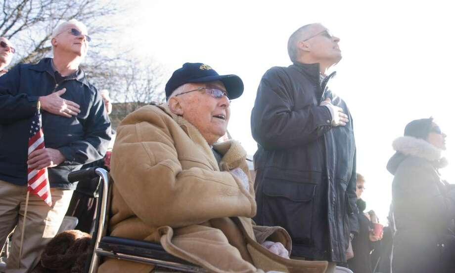 Pearl Harbor survivor James Benham, 92, center, sings the National Anthem during a Pearl Harbor remembrance ceremony at Veteran's Park in Stamford, Conn. on Sunday, Dec. 6, 2009. After Elwood Lichack died earlier this year, Benham became the last known Pearl Harbor survivor in lower Fairfield County. Photo: Chris Preovolos / Stamford Advocate