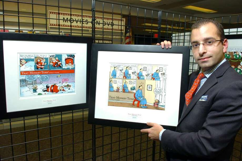 "Michael Kandalaft, creator of ""That Monkey Tune"" comic, poses with some of his art work, which is on display at the Stratford Public Library, in Stratford, Conn. Nov. 30th, 2009. Photo: Ned Gerard / Connecticut Post"