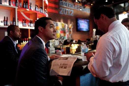 Mayor Julian Castro watches the news and reads USA Today featuring a story about his speech, as he waits with his brother, Joaquin Castro, right, to appear on CNN's morning news program Starting Point with anchor Soledad O'Brien at the CNN Grill during the Democratic National Convention in Charlotte, NC on Wednesday, Sept. 5, 2012. Photo: Lisa Krantz, San Antonio Express-News / San Antonio Express-News