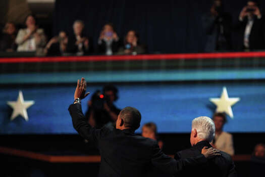 Former President Bill Clinton and President Barack Obama leave the stage after sharing a brief moment and hug after Clinton's speech during the Democratic National Convention at Time Warner Cable Arena in Charlotte, NC on Wednesday, Sept. 5, 2012. Photo: Lisa Krantz, San Antonio Express-News / San Antonio Express-News