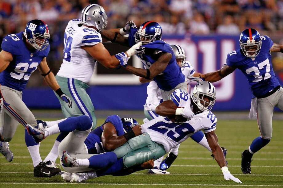 EAST RUTHERFORD, NJ - SEPTEMBER 05:  linebacker Keith Rivers #55 of the New York Giants tackles running back DeMarco Murray #29 of the Dallas Cowboys during the 2012 NFL season opener at MetLife Stadium on September 5, 2012 in East Rutherford, New Jersey. Photo: Jeff Zelevansky, Getty Images / 2012 Getty Images