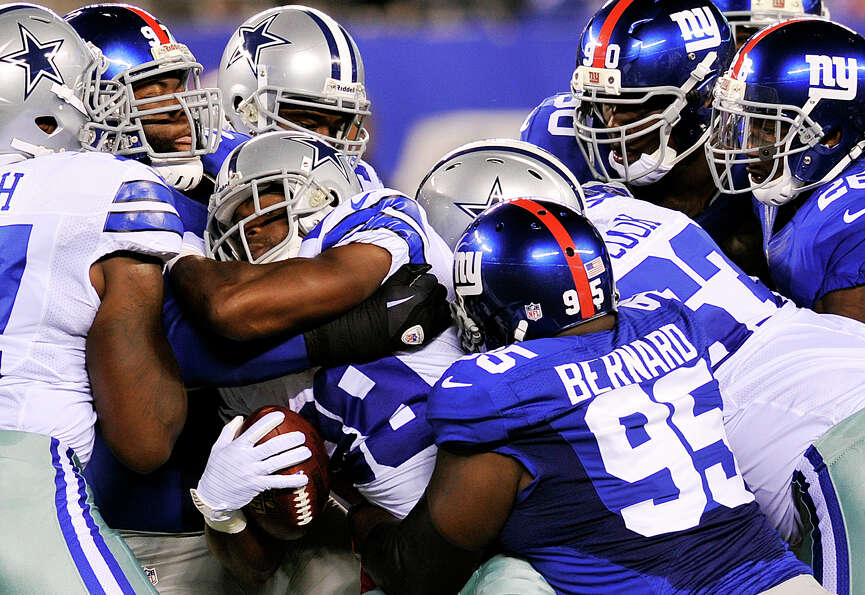 Dallas Cowboys running back Felix Jones (28) is tackled by New York Giants defensive tackle Rocky Be