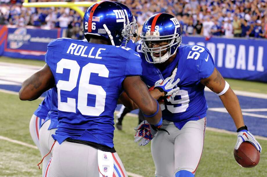 New York Giants linebacker Michael Boley (59) celebrates with Antrel Rolle (26) after intercepting a pass during the first half of an NFL football game against the Dallas Cowboys, Wednesday, Sept. 5, 2012, in East Rutherford, N.J. Photo: Bill Kostroun, AP / FR59151 AP