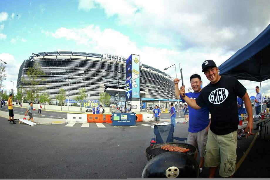 EAST RUTHERFORD, NJ - SEPTEMBER 05:  Fans of the New York Giants pose for a photo while barbequing outside of MetLife Stadium prior to the 2012 NFL season opener between the New York Giants and the Dallas Cowboys on September 5, 2012 in East Rutherford, New Jersey. Photo: Al Bello, Getty Images / 2012 Getty Images